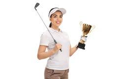 摆在与高尔夫俱乐部和金战利品的女性高尔夫球运动员 库存图片