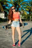 摆在与滑板的溜冰者女孩在海滩的棕榈附近 五颜六色的clothers的妇女 库存照片