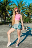 摆在与滑板的美丽和时尚少妇在棕榈附近 免版税库存照片