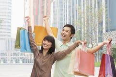 摆在与购物袋的年轻夫妇画象在手上,北京,中国 免版税图库摄影