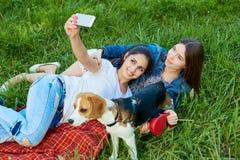 摆在与他们的狗的两个可爱的女孩在公园 免版税库存照片