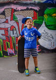 摆在与他的滑板的愉快的年轻男孩 库存图片