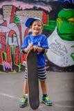 摆在与他的滑板的愉快的年轻男孩 免版税库存照片