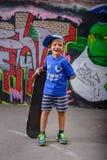 摆在与他的滑板的愉快的年轻男孩 免版税库存图片