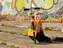 摆在与他的滑行车的愉快的小男孩 图库摄影