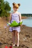 摆在与绿皮书小船的微笑的小女孩 免版税库存图片