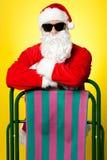 摆在与deckchair的时髦的男性圣诞老人 免版税图库摄影