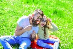 摆在与eyeglases照片摊属性的孩子和父亲在草甸 聪明和聪明的概念 爸爸和女儿坐 库存图片