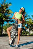 摆在与longboard的被晒黑的妇女全长画象在棕榈附近在热带国家 免版税库存图片