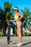 摆在与longboard的被晒黑的妇女全长画象在棕榈附近在热带国家 免版税图库摄影