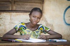 摆在为一个教育射击标志的非洲学校女孩 免版税库存图片
