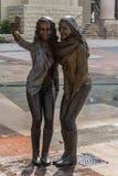 摆在为一张selfie照片的两个女孩雕象在舒格兰,TX 免版税库存照片