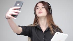 摆在为与智能手机的一张selfie照片的耳机的悦目少妇 股票视频