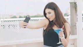 摆在为与觚的selfie的女孩在海滩的蓝色鸡尾酒 影视素材