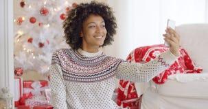 摆在为圣诞节selfie的愉快的少妇 免版税库存图片