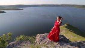 摆在为在巨大的河岸边缘的照相机的红色礼服的美丽的黑发妇女 股票视频