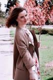 摆在为在背景sakuras的一张照片的女孩 图库摄影