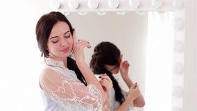 摆在为在镜子、女孩有桃红色嘴唇的和钉子前面的照相机的感人的软的面颊妇女 影视素材