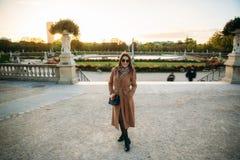 摆在为摄影师的外套的时髦的女孩 公园 库存图片