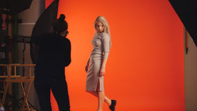 摆在为摄影师的白肤金发的女孩-模型在红色背景附近站立 免版税图库摄影