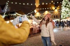 摆在为智能手机的愉快的妇女在圣诞节 库存图片