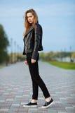 摆在为模型试验的黑皮夹克黑色牛仔裤易穿脱的衣服的愉快的年轻美丽的妇女在夏天公园 免版税库存图片