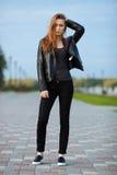 摆在为模型试验的黑皮夹克黑色牛仔裤易穿脱的衣服的愉快的年轻美丽的妇女在夏天公园 免版税库存照片