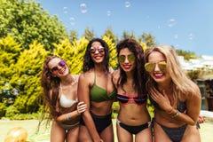 摆在为照片的女性朋友在游泳池边 免版税库存照片