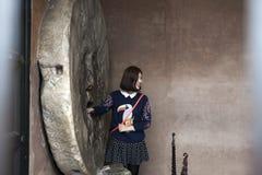 摆在为照片的妇女游人在著名Bocca della Verita雕塑,罗马,意大利 免版税库存照片