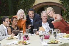 摆在为照片的小组在室外餐桌上 免版税库存照片