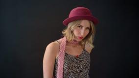 摆在为照片的桃红色帽子的年轻白肤金发的妇女,站立隔绝在黑演播室背景 股票视频