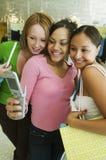 摆在为照相机在服装店的电话图片的3个女朋友 库存图片