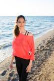 摆在为照相机的一名年轻可爱的适合妇女的画象,当站立在海滩在晴朗的夏日时 免版税库存图片