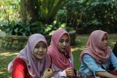 摆在为照相机的三个女孩在植物园里 免版税库存照片