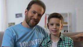 摆在为照相机的人和男孩,孤儿的,收养志愿参观的小孩 股票视频