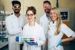 摆在为照相机的小组年轻成功的科学家 免版税库存照片