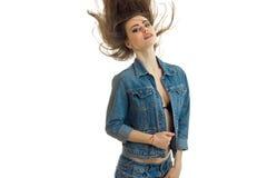 摆在为照相机的牛仔裤夹克的美丽的女孩和她的头发通过空气飞行 库存照片