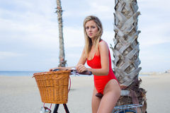 摆在为照相机的红色比基尼泳装的诱人的女性户外 免版税库存照片