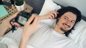 摆在为照相机的英俊的浅黑肤色的男人在床上,当妇女照相在家时 股票录像