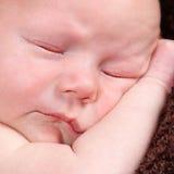 摆在为照相机的逗人喜爱的矮小的新出生的男婴 免版税库存照片