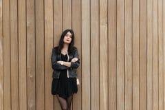 摆在为照相机的年轻欧洲妇女半身画象,当站立反对与拷贝空间a时的木墙壁背景 库存照片