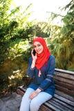 摆在为照相机的hijab的美丽的年轻阿拉伯女孩在夏天街道 免版税库存照片