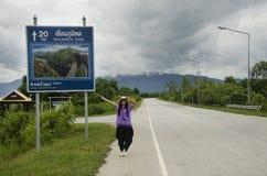 摆在为的泰国妇女旅客拍与距离标志指南杆的照片 库存照片