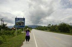 摆在为的泰国妇女旅客拍与距离标志指南杆的照片 免版税库存照片