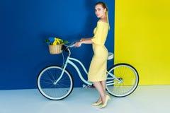 摆在乘有花的自行车的典雅的白肤金发的妇女在蓝色的篮子 免版税库存照片