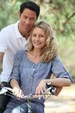 摆在乘自行车的夫妇 库存照片