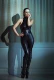摆在乳汁catsuit的性感的妇女 免版税库存照片