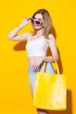 摆在五颜六色的上面和裙子的时兴的现代女孩有大黄色袋子的在她的手上在黄色背景在演播室 Fashi 免版税库存图片