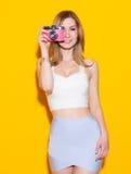 摆在五颜六色的上面和裙子的时兴的现代女孩有葡萄酒照相机的在她的手上黄色背景在演播室 作为 免版税库存图片