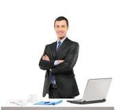 摆在他的工作场所的一个确信的生意人 免版税库存照片